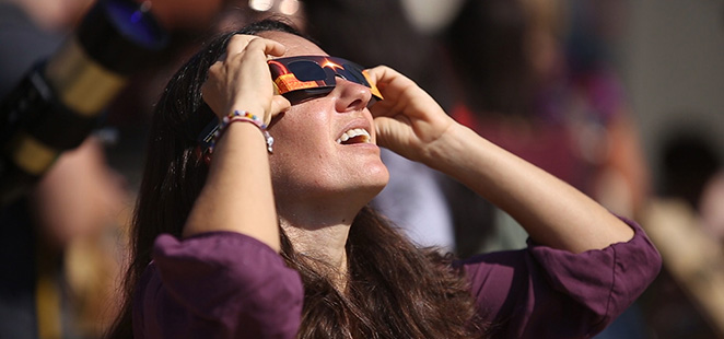 A City College professor looks at the eclipse with special eclipse glasses
