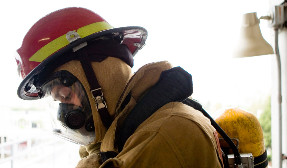 Firefighter wears a helmet and mask
