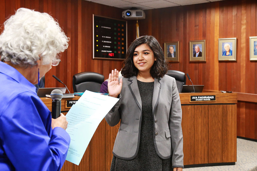 a student is sworn in as a student trustee at a board meeting