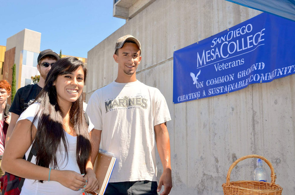 Students on steps at mesa college next to a military friendly sign