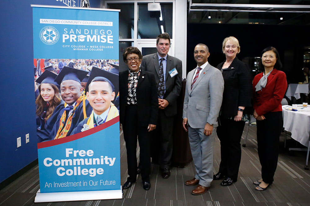 the chancellor and college and ce presidents stand next to a promise banner