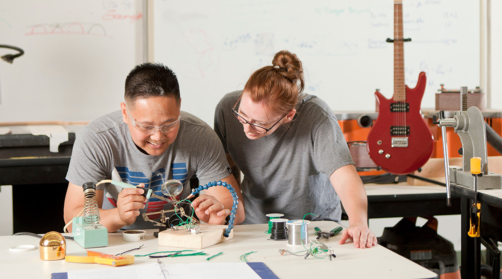 Two students work together in a guitar-building course