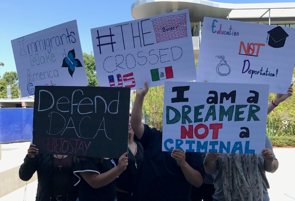 DACA students hold protest signs