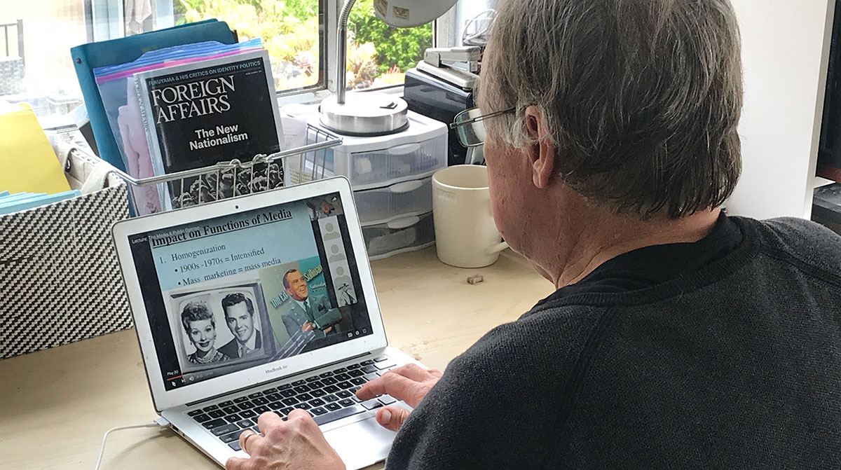 A professor at his computer putting together an online lesson